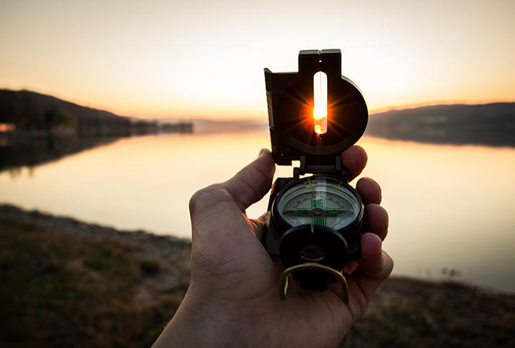 How to Course-Correct Your Future by Dain Heer. Photograph of a hand holding a compass in the sun, by Tim Graf.