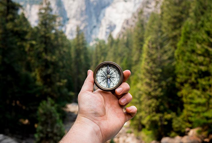 How to Find Your Ikigai and Live a Life of Happiness & Purpose by Emily Gibson. Photograph of a man holding a compass in nature by Jamie Street