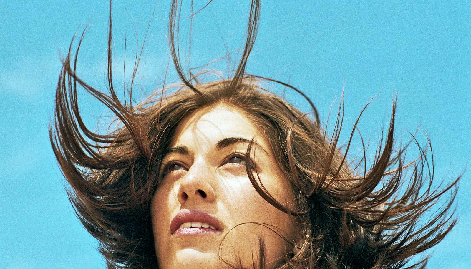 A woman looks off into the distance while her hair blows around