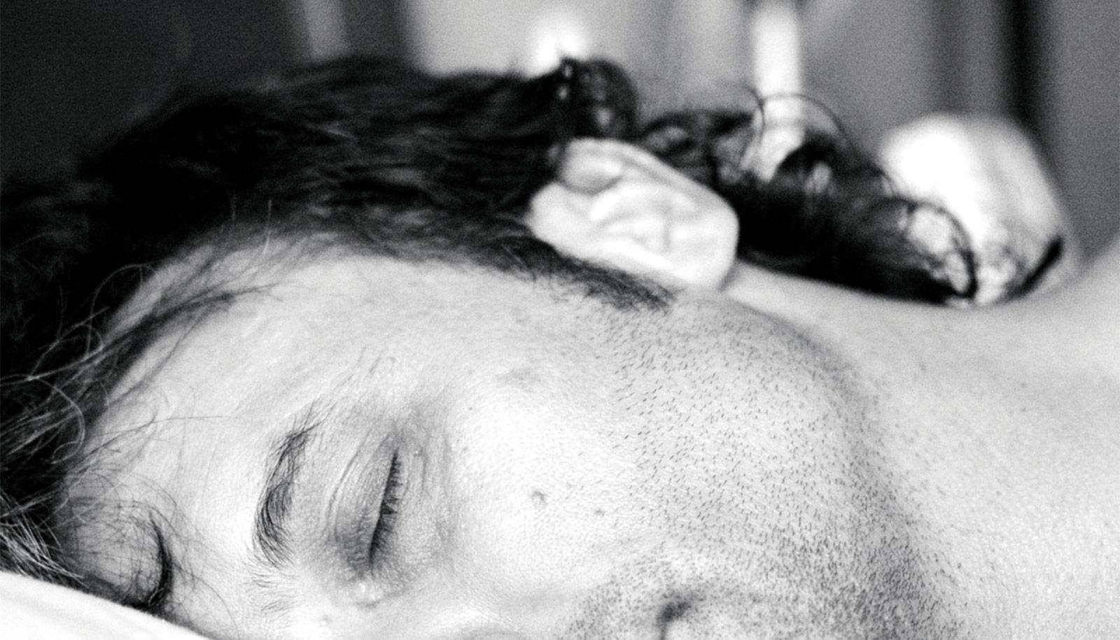 A man sleeping with half his face out of frame