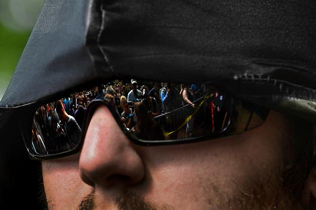 A crowd of protestors are reflected in the sunglasses of a member of the Ku Klux Klan in Justice Park in Charlottesville, Virginia. (Michael S. Williamson/The Washington Post via Getty Images)