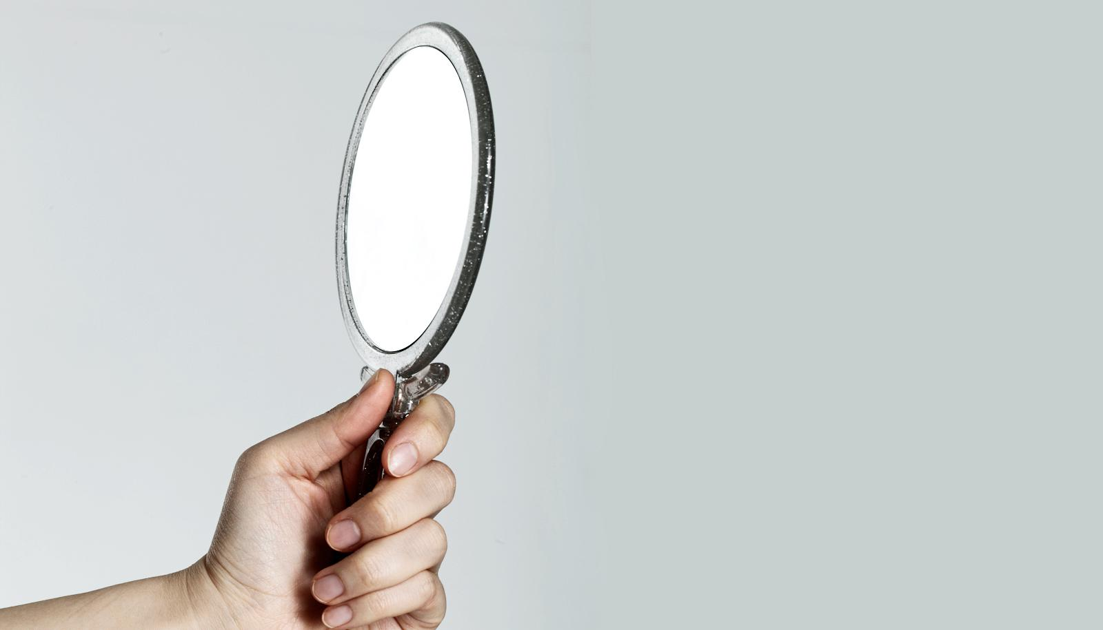 mirror in hand on gray - appearance