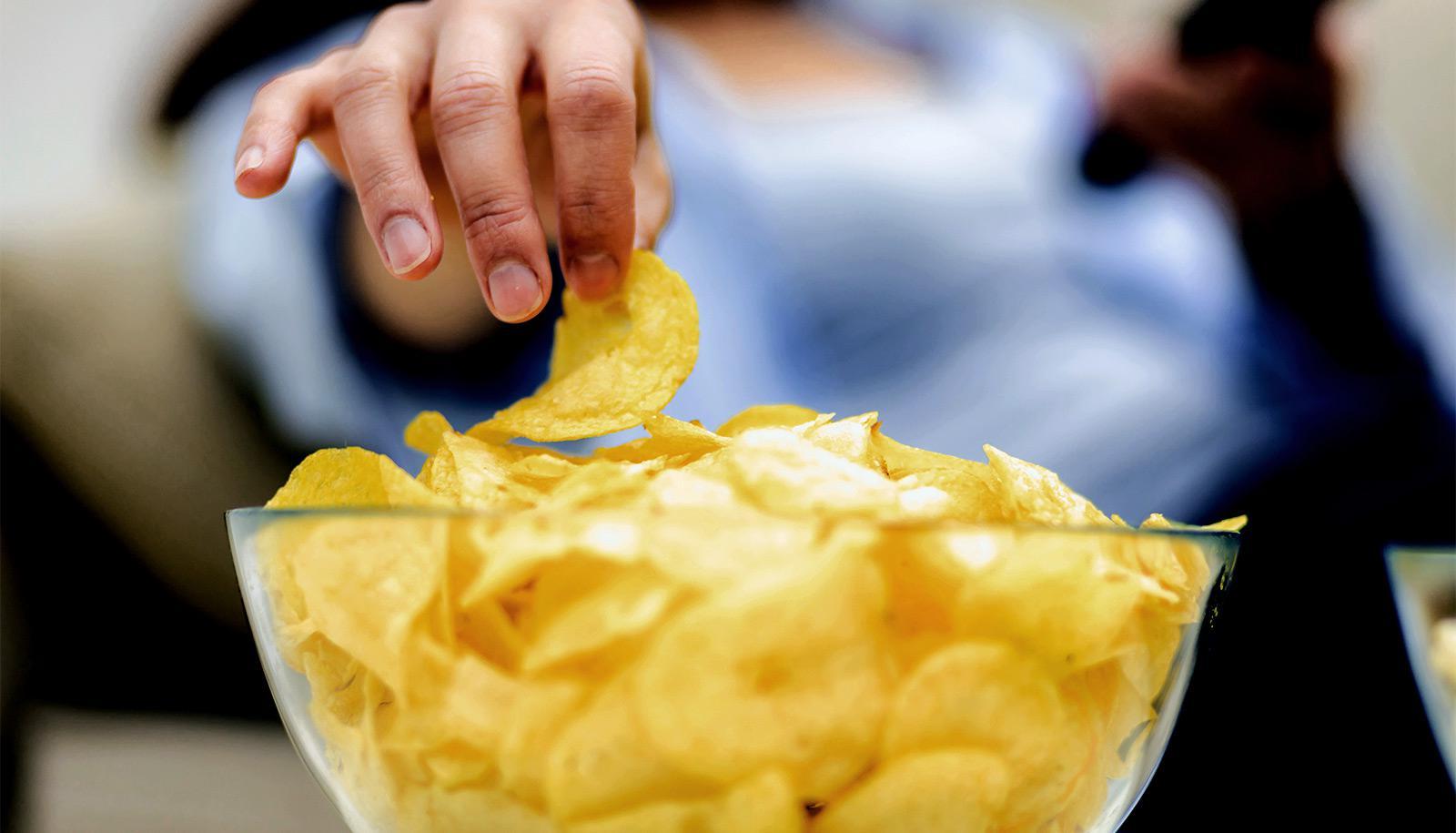 A woman grabs a potato chip from a bowl