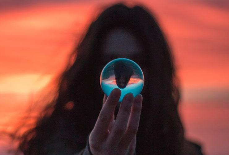 Clean Thoughts: 3 Principles of Information Hygiene for a Happy & Productive Life by Kristin Goad. Photograph of a woman looking into a crystal ball by Garidy Sanders