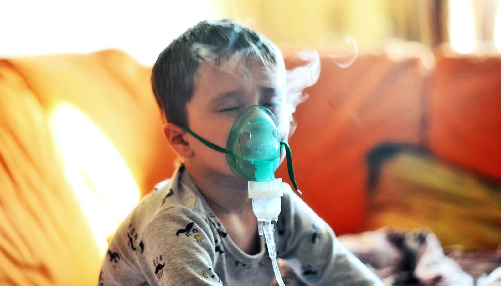 A boy breathes through a nebulizer