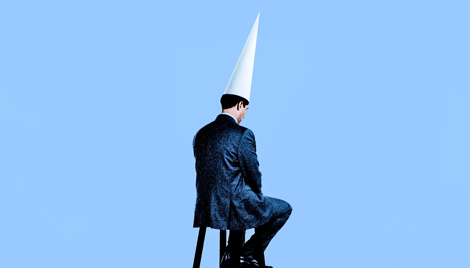 man sitting in dunce hat (artificial intelligence concept)