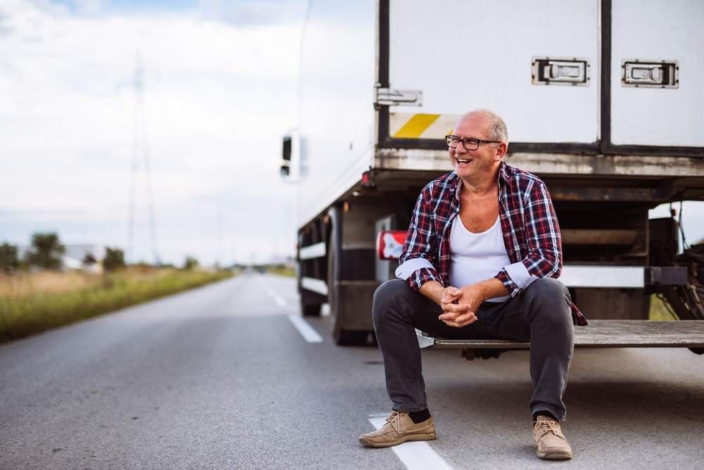 man sitting next to a truck