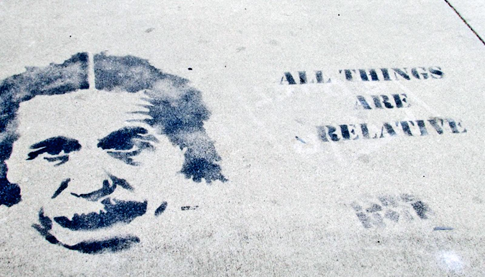 """A print of Einstein's face on pavement with the words """"All things are relative"""" stamped nearby"""