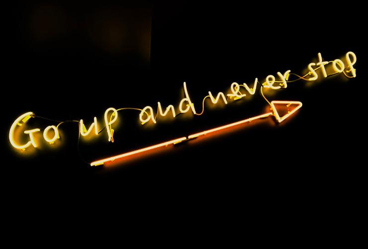 "Want to Succeed? Stop Planning to Fail by Elena Blanco. Photograph of a neon sign that reads ""Go up and never stop"" by Fab Lentz"