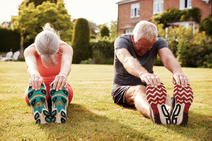 Health-Boosting, Low-Impact Exercises for Seniors, by Jenny Hart. Photograph of two seniors stretching on lawn by Monkey Business