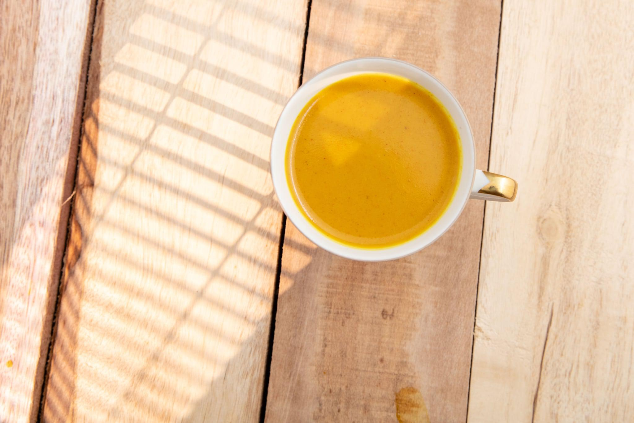 Hot turmeric latte. Served in white cup. Wooden plank. High point of view.
