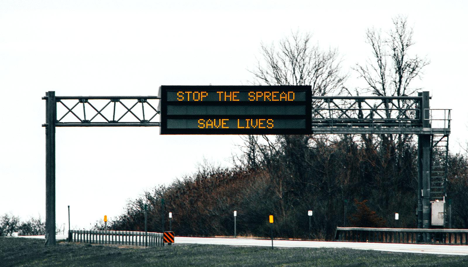 """sign over highway says """"stop the spread save lives"""""""
