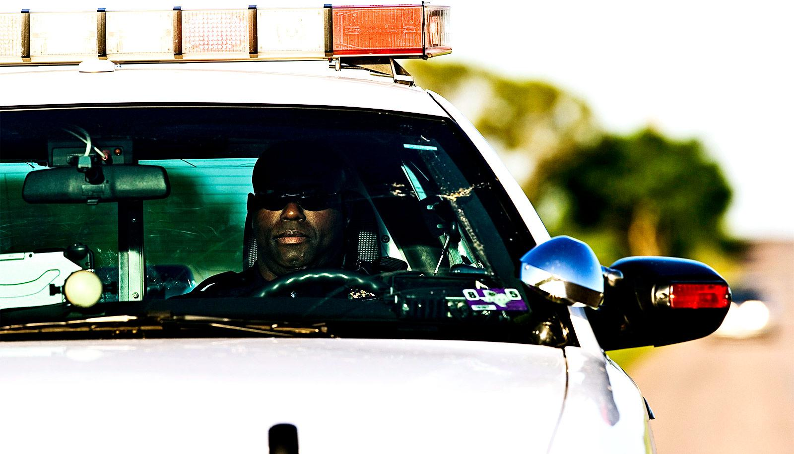 A police officer sits in a squad car