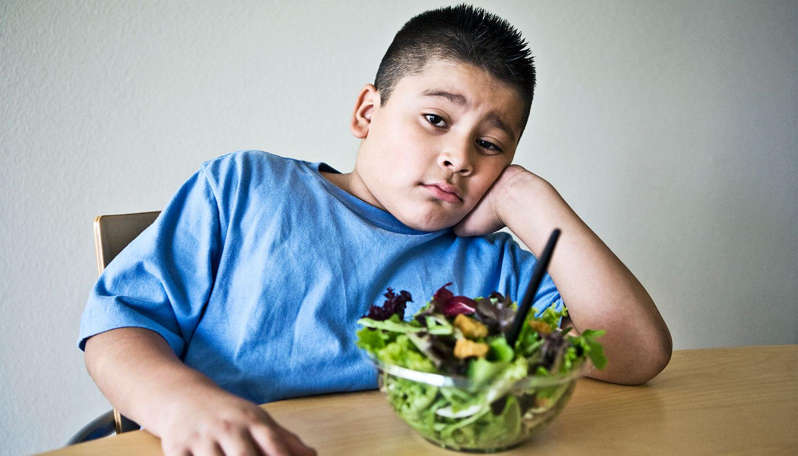 A young boy in a blue shirt sits in front of a bowl of salad with a skeptical or disappointed look