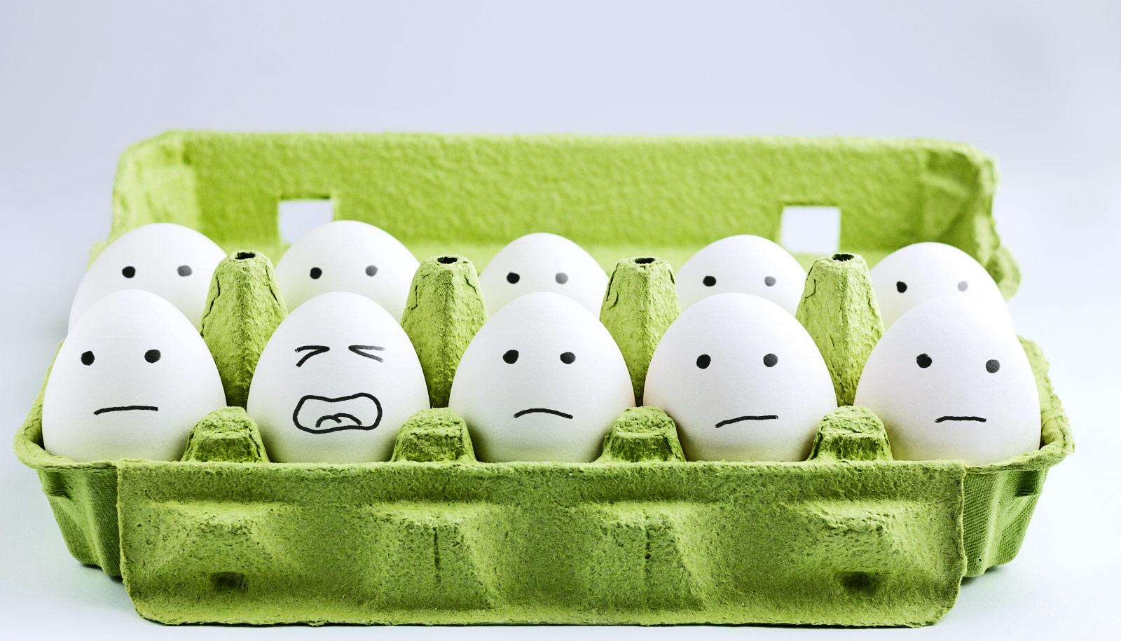 eggs with sad faces in green carton