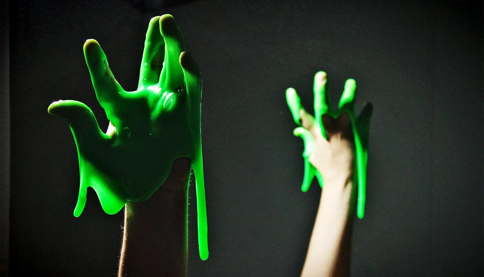 Bright green slime drips from a hand, which is also mirrored in the background