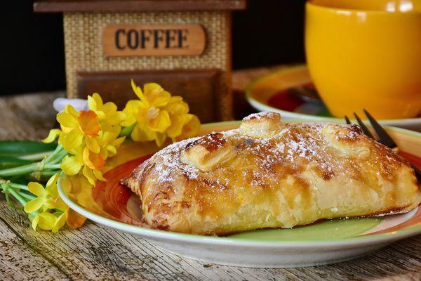 flowers brakfast pastry on a plate mug fork coffee