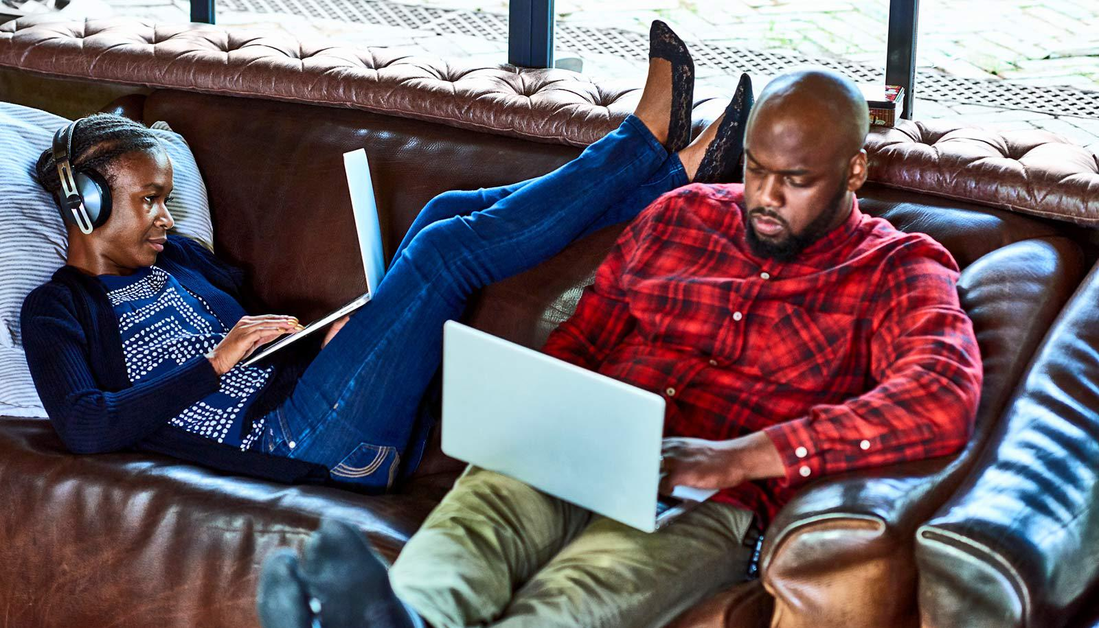 two people use laptops on couch