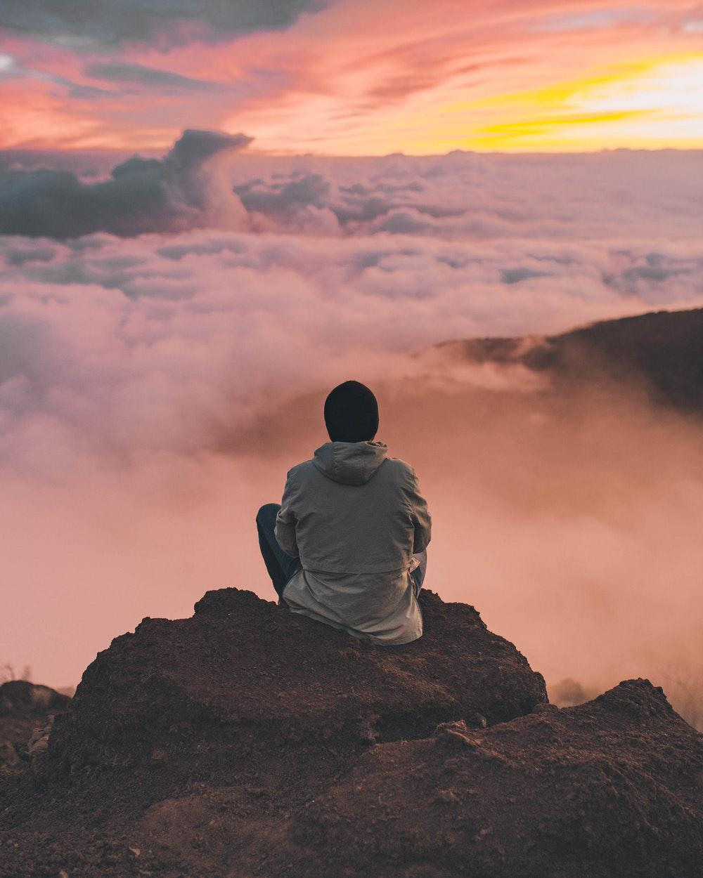 Forgiveness: The Path to Embracing My Lion Heart by Laura Bishop. Photograph of man on cliff looking over clouds and sunset by Ian Stauffer