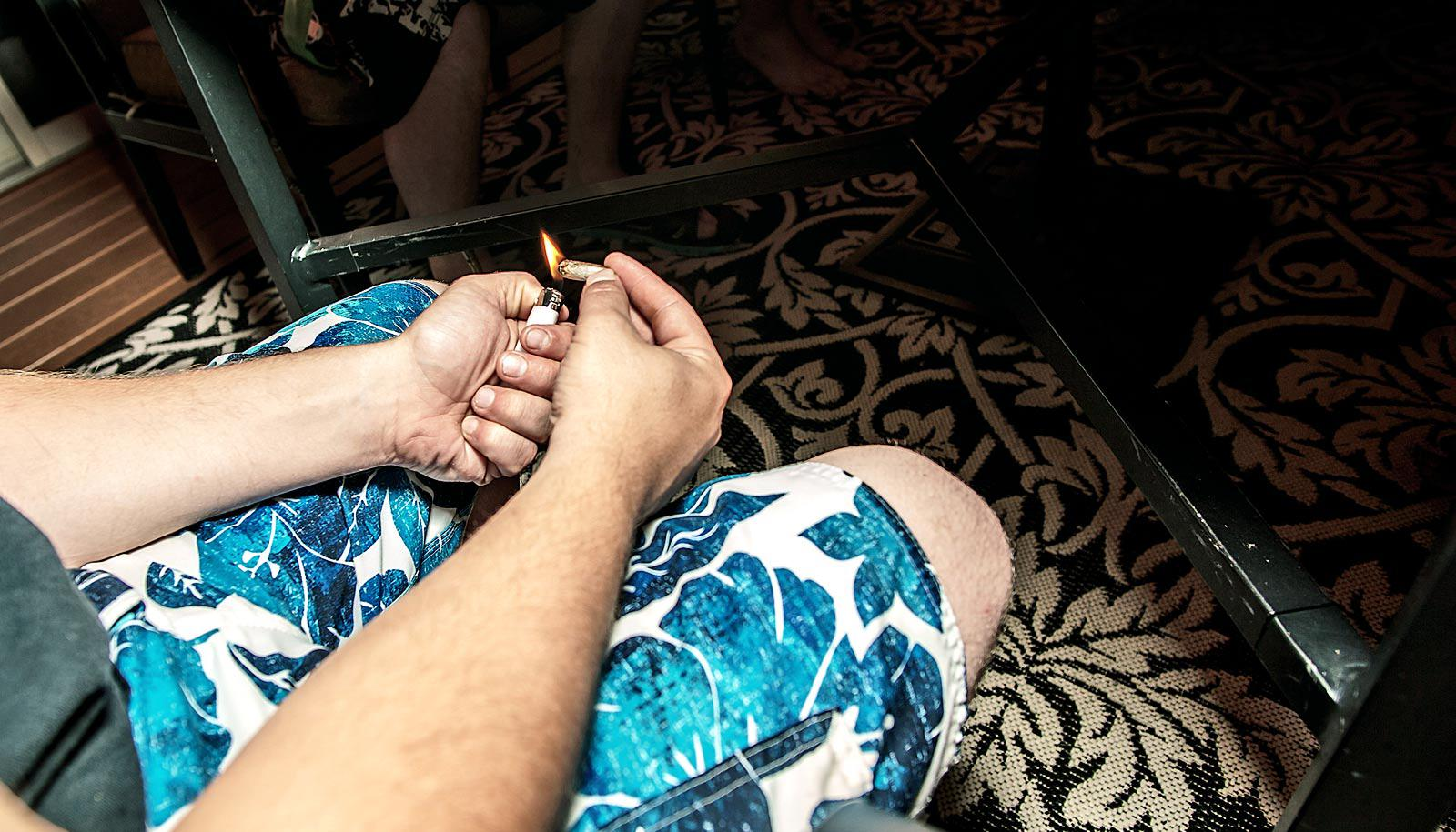 man holds lighter and blunt under table