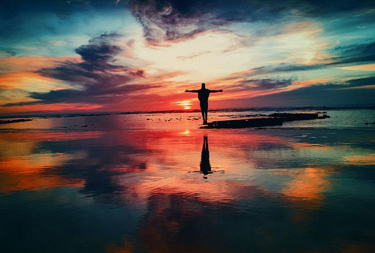 How to Take Control of Your Life and Begin Living Consciously by Damien Justus. Photograph of a man standing in the water during a sunset by Mohammed Nohassi