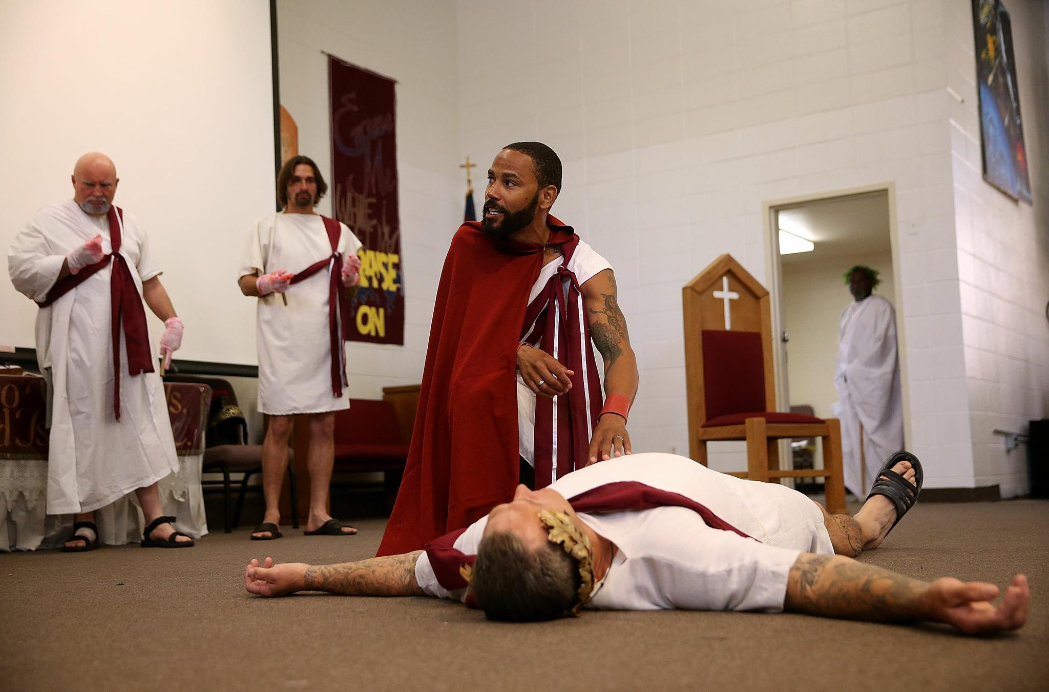 San Quentin State Prison inmate LeMar Harrison, center, plays Mark Antony in a production of Shakespeare's Julius Caesar at San Quentin State Prison on May 15, 2015. Under the direction of Shakespeare for Social Justice, San Quentin State Prison inmates are performing Shakespearean plays for inmates and a select audience of outside guests.