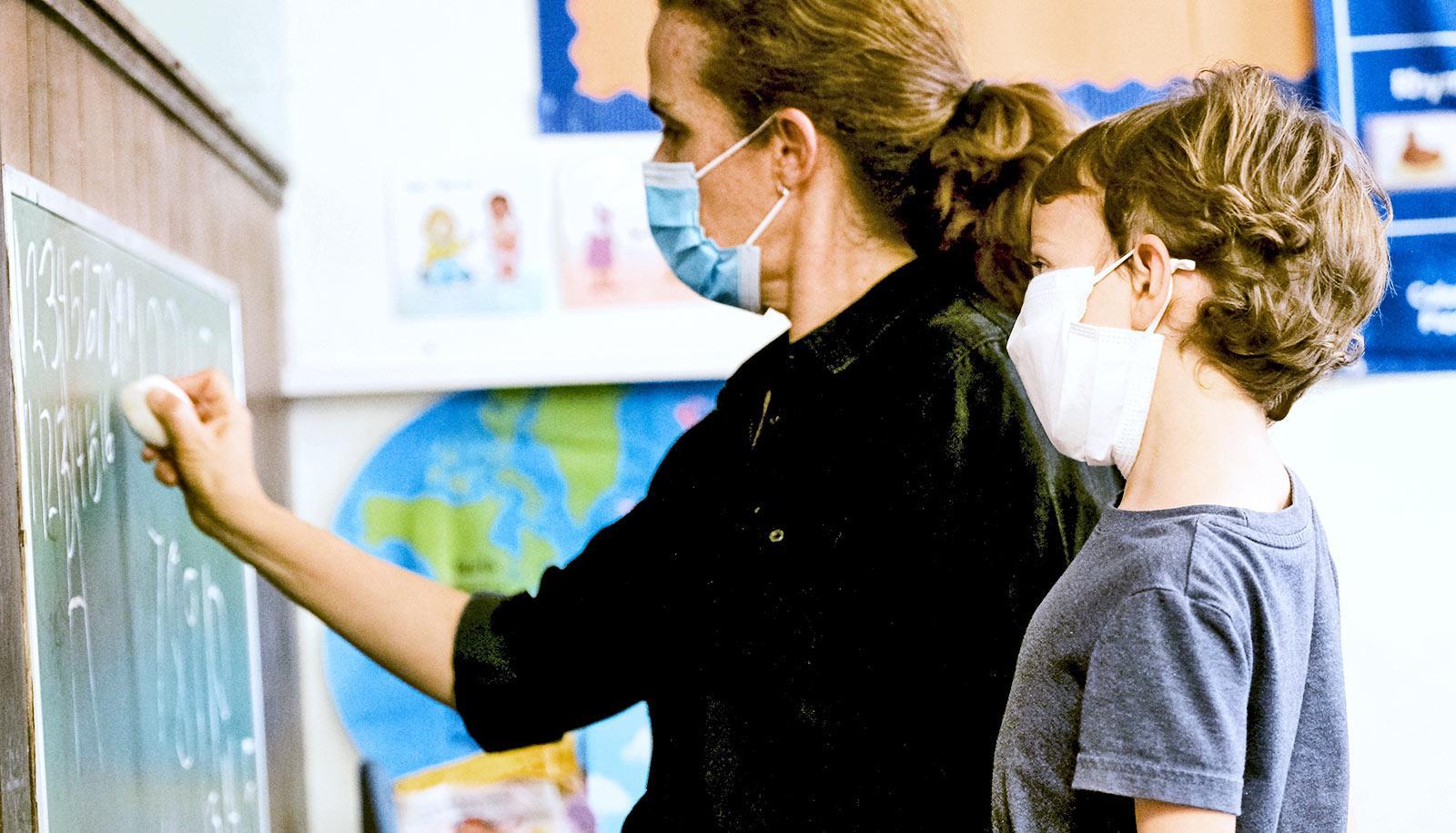 A preschool teacher kneels at a chalkboard next to a young boy