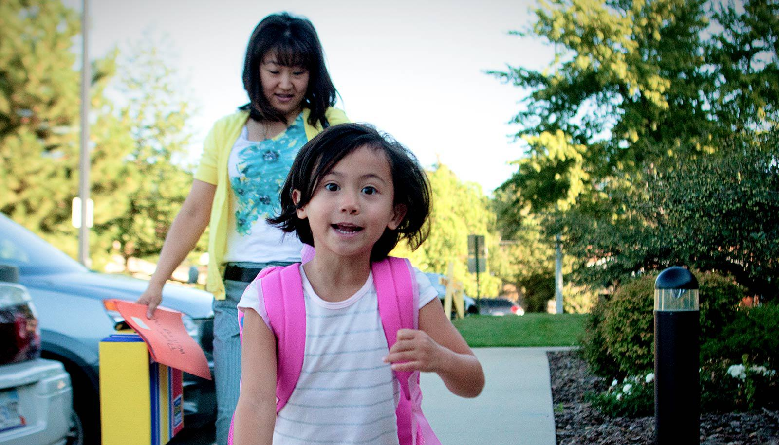 excited child runs toward camera with mother behind carrying folder