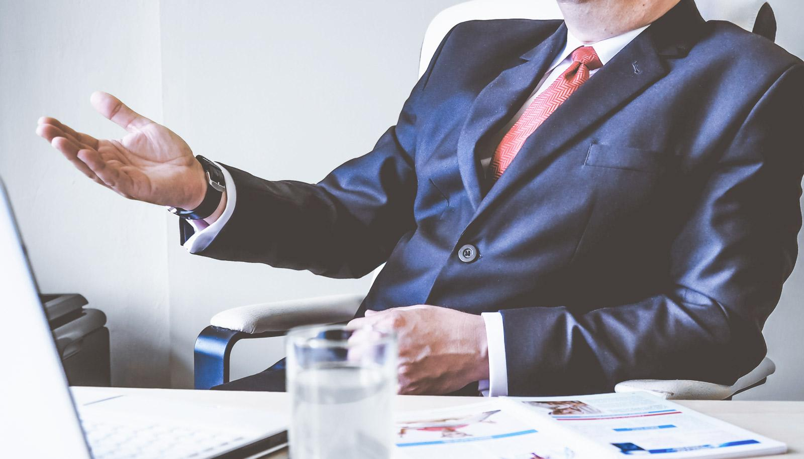 man in suit at desk gestures