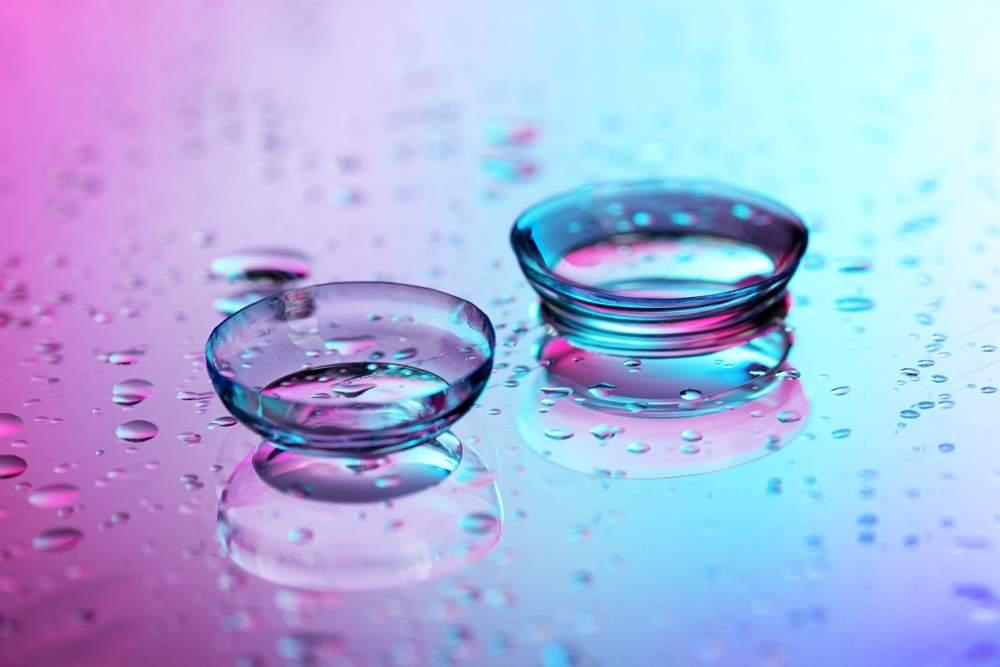 two contact lenses on a pink and blue background