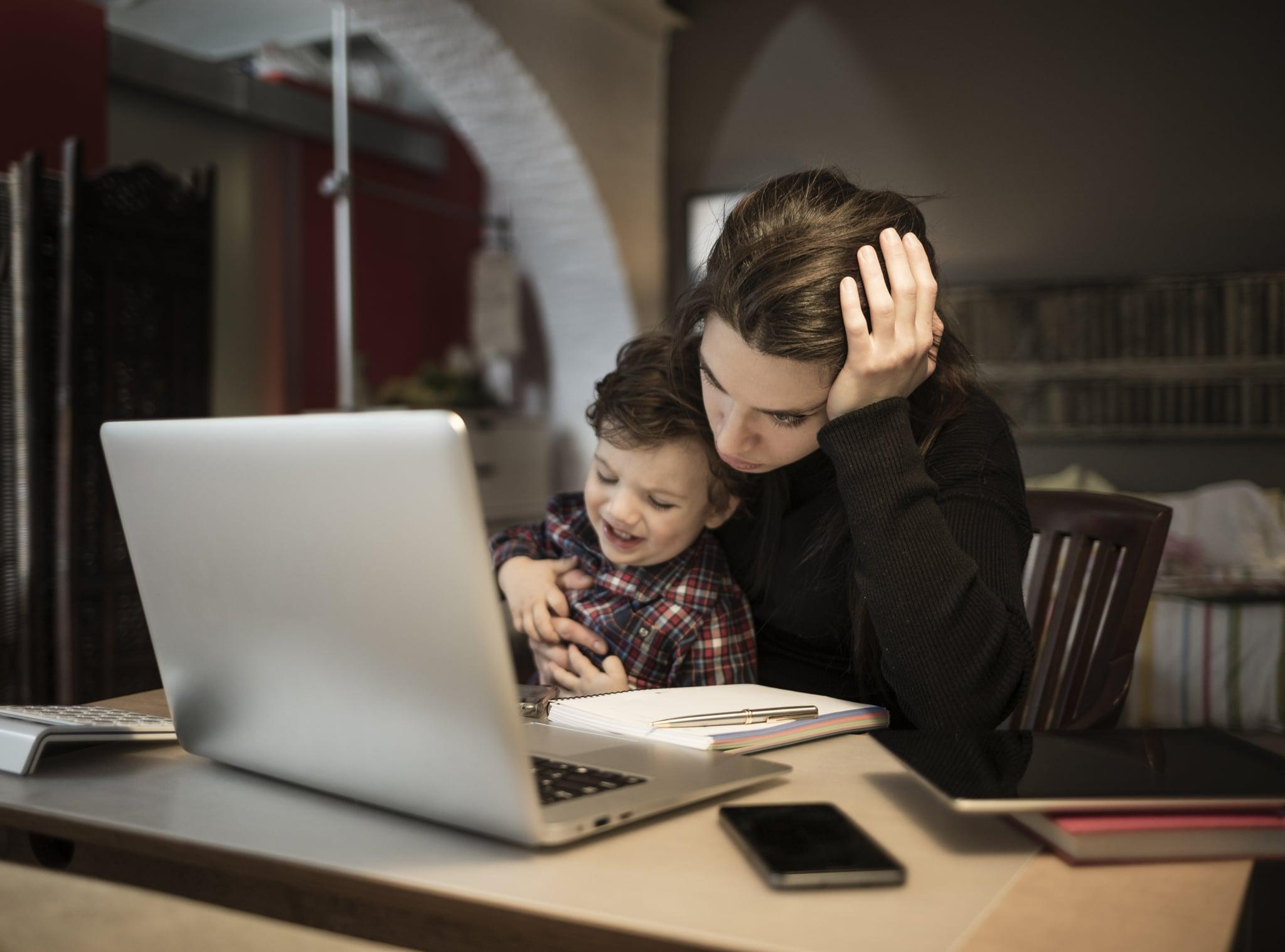 Worried woman working at home and holding her crying little son
