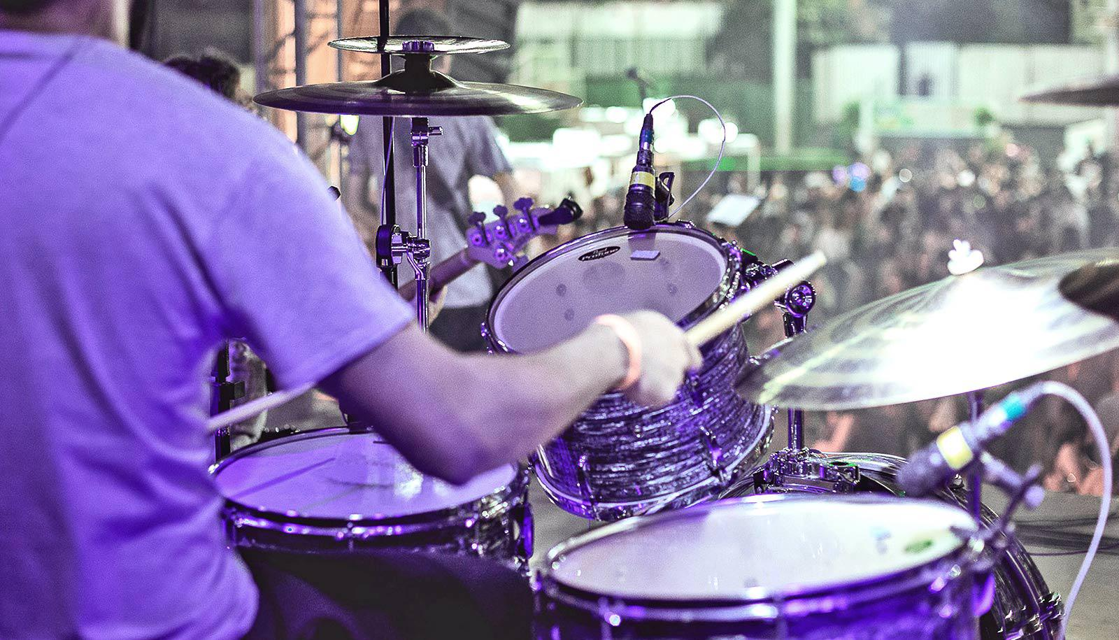 A drummer plays on stage for a crowd